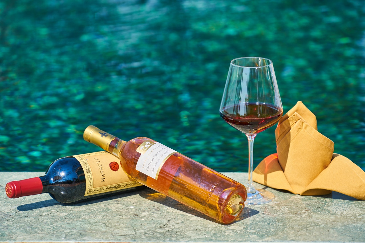 bottles of wine next to a pool