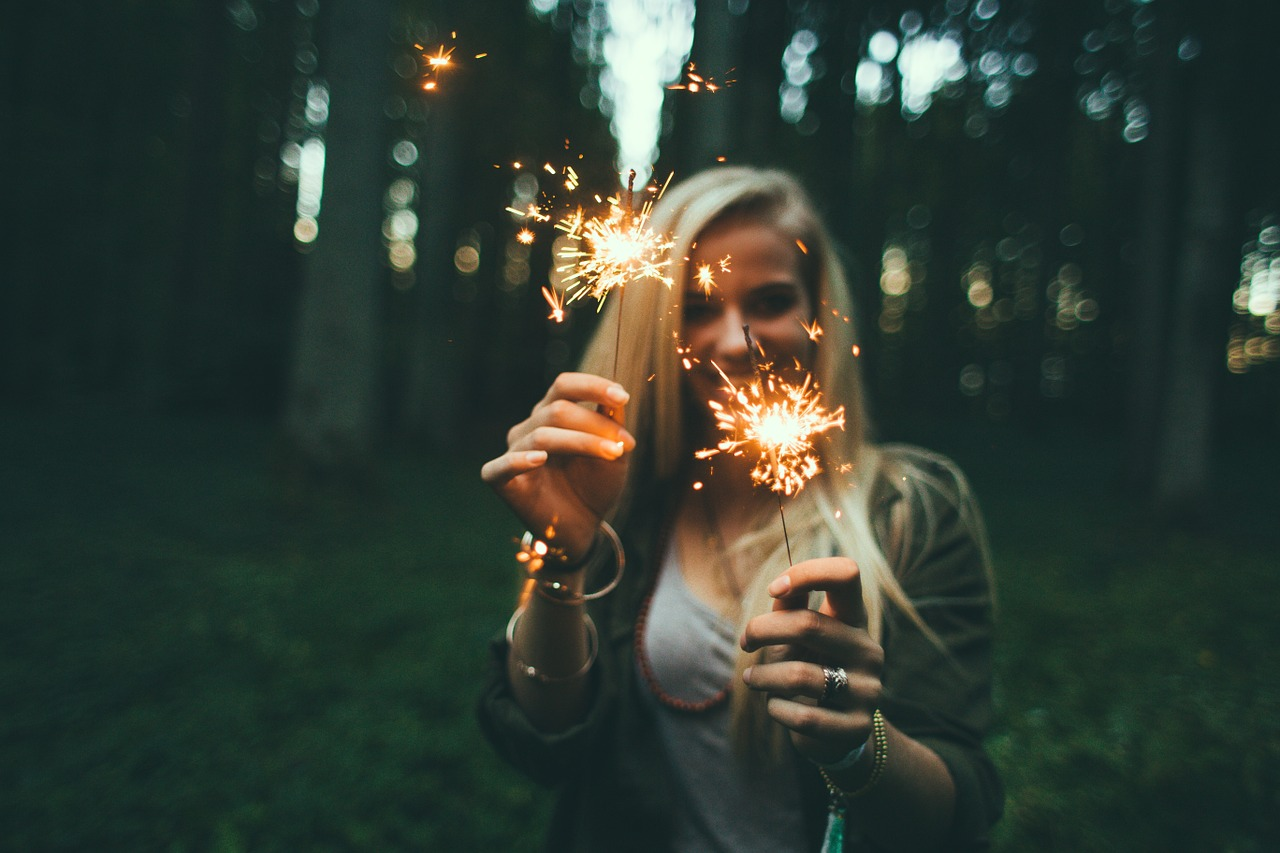 a woman holding glowing sticks